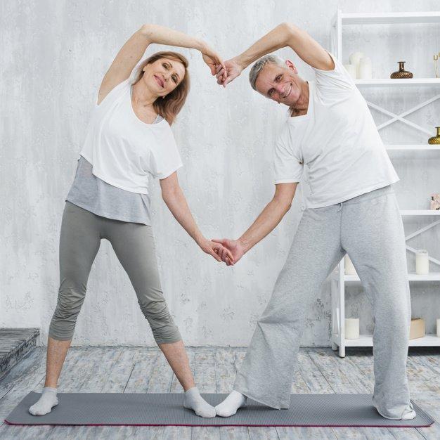 A happy elder couple standing in yoga pose