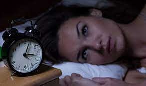 A woman is laying in her bed with open eyes and looking at something