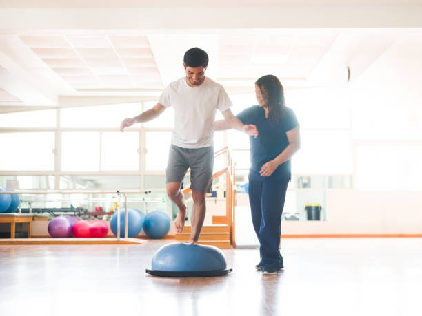 A young latin man standing on an balance trainer with one leg next to a female occupational therapist in a physical therapy room.