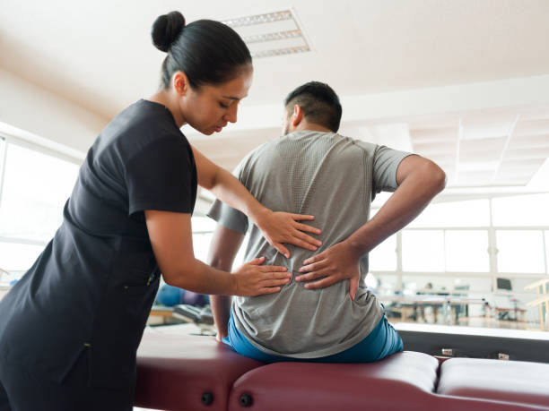 A female massage therapist standing behind a male patient and massaging his back with both hands.