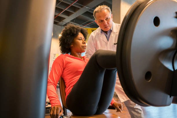 Afro-Colombian woman with her doctor in a gym. In the image he appears with his doctor, who explains the rehabilitation exercises that he must do.