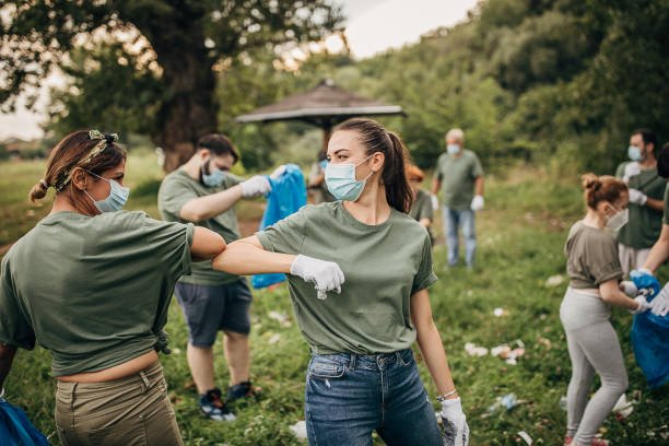Group of people, cleaning together in public park, saving the environment together, all of them are wearing surgical masks do to coronavirus.