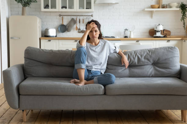 Tired upset woman worried about tiredness from domestic work sitting at couch. Frustrating mom stressful feels heaviness and headache at home. Fatigue parent trying relaxing in living room.