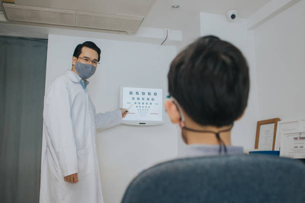 Portrait of a non-Caucasian optician man asking the boy for an eye exam test with an eye chart monitor at his clinic, Bangkok Thailand