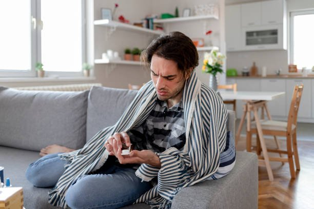 Man With Fever Wrapped in a Warm Blanket Suffering Cold and Flu at Home
