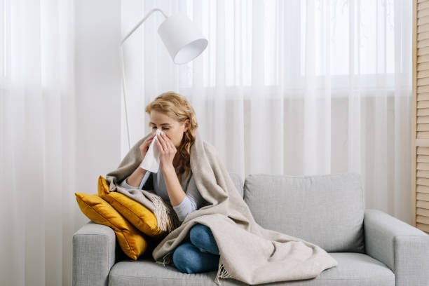 Respiratory infection concept. Sick woman got fever, flu and influenza disease, blowing running nose. Female covered in plaid, sit on sofa at home, cough and sneezing in tissue