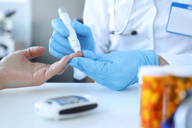 Doctor piercing patients finger with lancet in clinic closeup. Blood glucose control concept