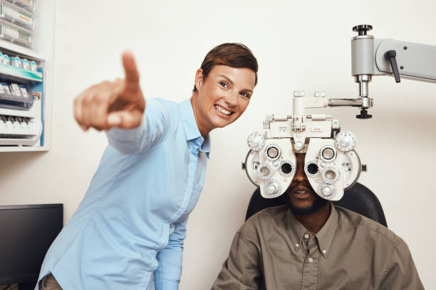 Shot of an optometrist examining her patient's eyes with an optical refractor