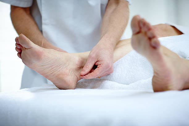 Physiotherapist doing acupuncture on the feet of a female patient lying on medical table