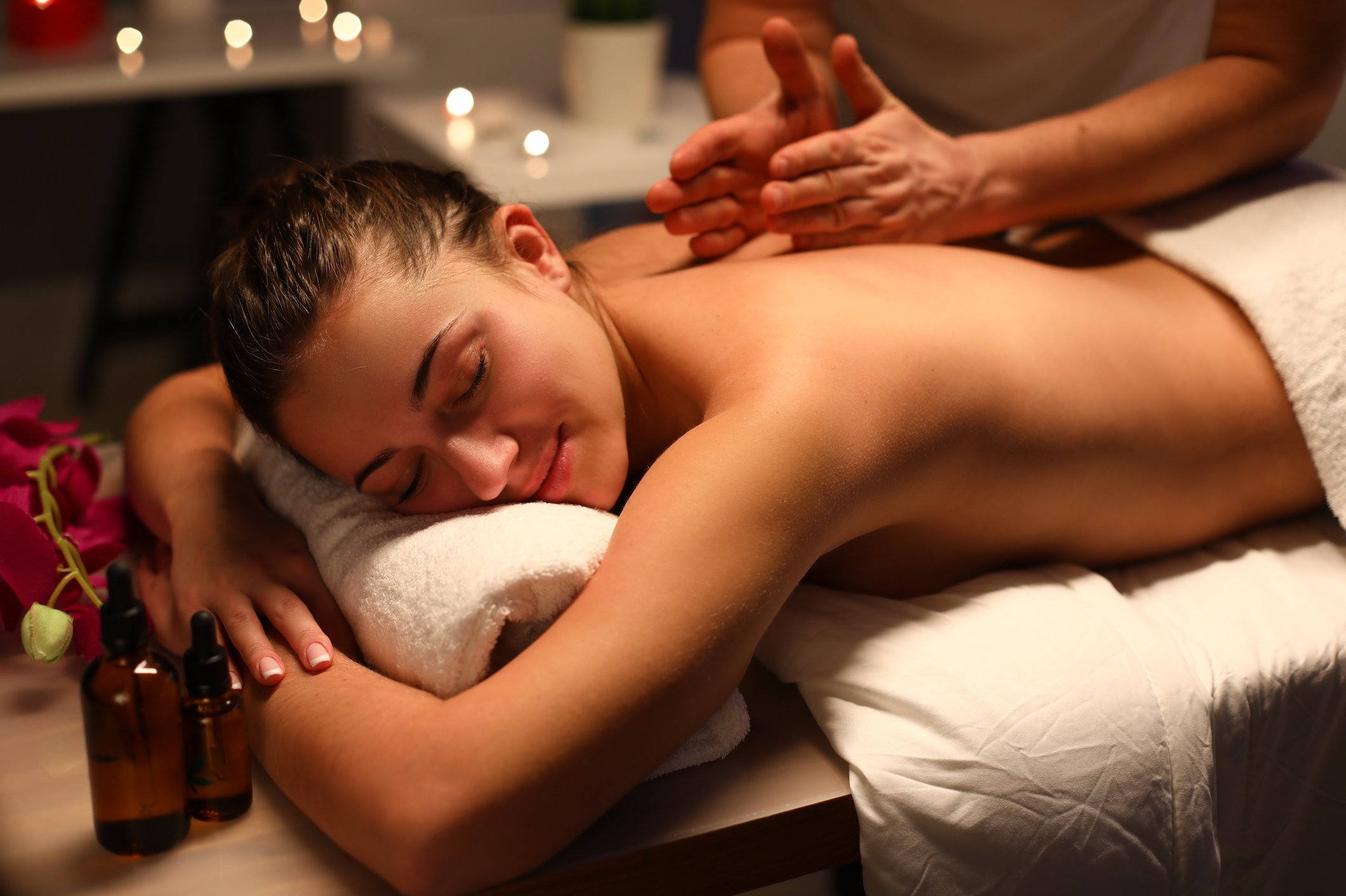 Masseur give wellness back massage to client in spa center.